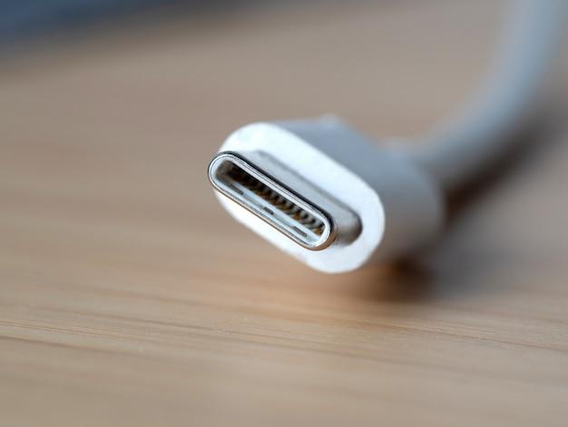 Белый провод типа c крупным планом на деревянном столе. новый usb-разъем для портативных устройств