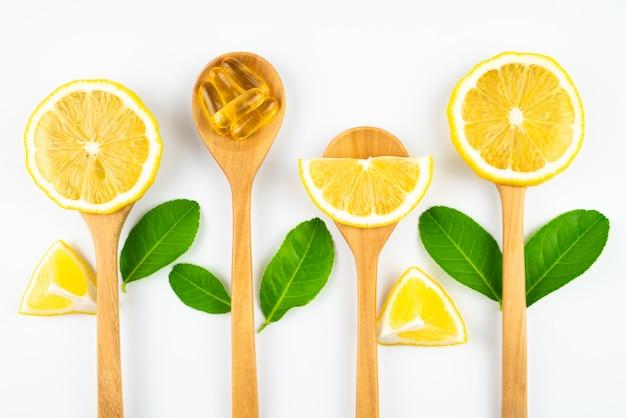 健康、医学、薬物の概念の木製スプーンサプリメントでレモンとビタミンcカプセルをスライスします。