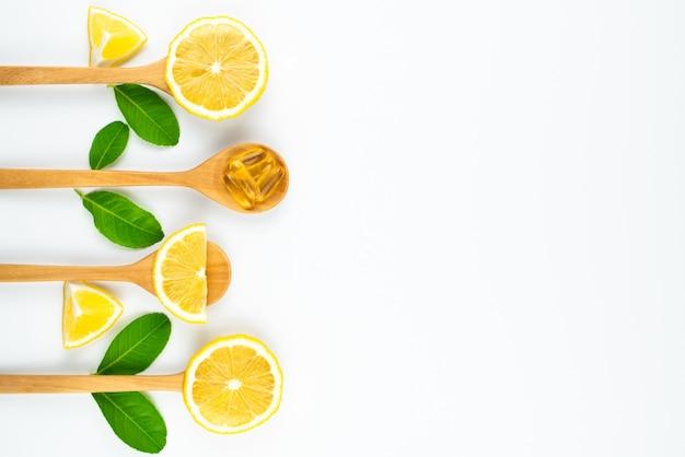 健康、白い背景、薬と薬の概念のための木製スプーンサプリメントでレモンとビタミンcカプセルをスライスします。
