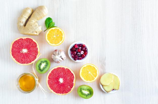 柑橘系の果物や明るい木製の背景にビタミンc製品のトップビュー半分