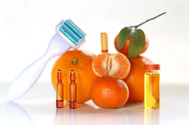 顔と体のメソセラピー。マッサージロール、マンダリンエッセンシャルオイル、オレンジとアンプル、ビタミンc、白い表面の柑橘類