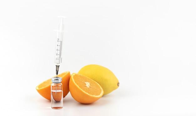 白い背景、オレンジ、レモンの薬と注射器します。医学と薬理学、ビタミンc、インフルエンザ、ウイルス、病気の予防の概念。