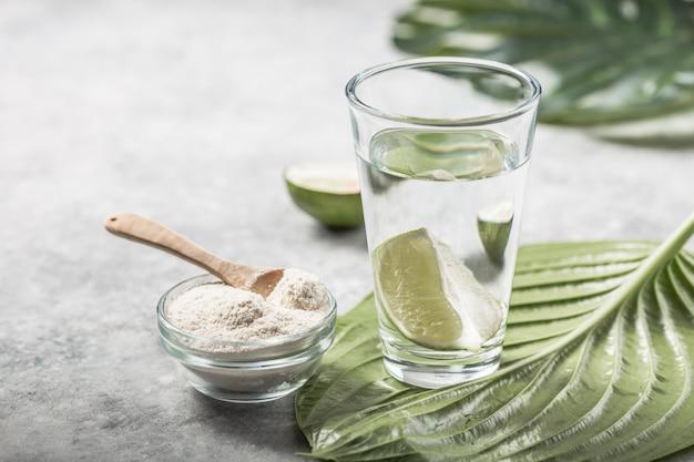 Коллагеновый порошок и стакан воды с ломтиком лайма; витамин c . добавки коллагена могут улучшить здоровье кожи, уменьшая морщины и сухость.