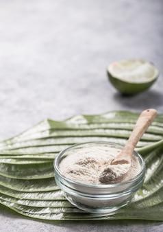 Коллагеновый порошок в стакане с ломтиком лайма; витамин c . добавки коллагена могут улучшить здоровье кожи, уменьшая морщины и сухость.