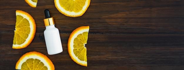 オレンジのフルーツエキスから作られた白いビタミンcのボトルとオイル、美容製品ブランドのモックアップ。木材の背景上の平面図です。