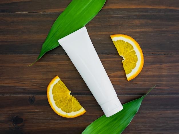 オレンジ色のフルーツエキス、フラットレイの美容製品ブランドのモックアップから作られた白いビタミンcボトルとオイル