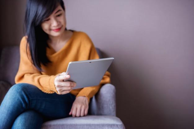 読書の概念。若い女性は、タブレットを使用して、居心地の良い家のソファーでリラックスして、cに座って