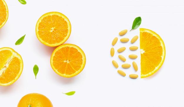 白で隔離される新鮮なオレンジの柑橘系の果物とビタミンcの丸薬
