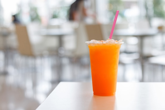 プラスチックガラスと白いテーブル背景にチューブのオレンジジュース。ビタミンcは健康に良い飲み物です。