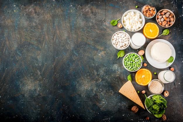 健康食品のコンセプト。カルシウム-乳製品とビーガンのca製品が豊富な食品のセット、暗い青色の表面コピースペース平面図背景