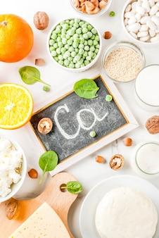 健康食品のコンセプト。カルシウムが豊富な食品のセット-乳製品とビーガンca製品の白い大理石の背景