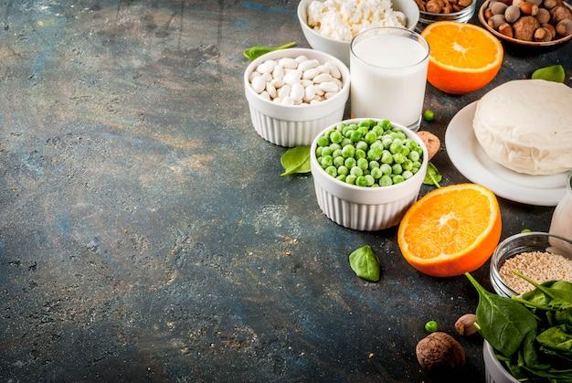 健康食品のコンセプト。カルシウムが豊富な食品のセット-乳製品とビーガンのca製品暗い青色の背景