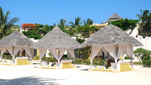 Кабана на пляже. роскошная жизнь. солнечный отдых на побережье занзибара.