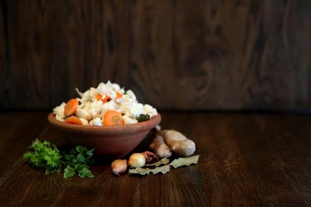 양배추와 당근 신선한 샐러드, 비건 샐러드 - 소박한 나무 배경에 있는 맛있고 맛있는 홈메이드 음식, 식사용 비타민 칵테일 요리. 파 또는 마늘 믹스