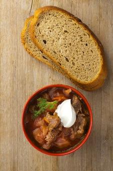 木製のテーブルトップビューにサワークリームとパンと赤いボウルのキャベツビートルートスープ