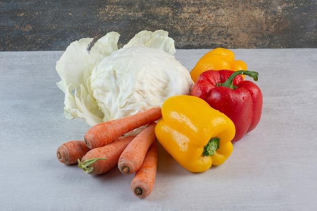 Капуста, морковь и сладкий перец на каменном столе. фото высокого качества