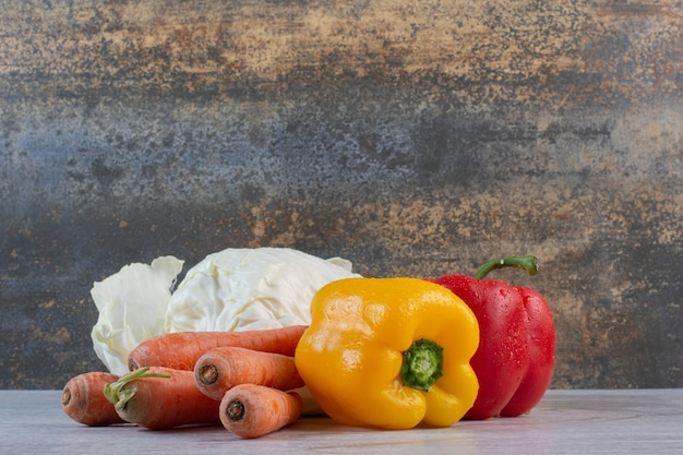 Cavolo, carote e peperoni sul tavolo di pietra. foto di alta qualità