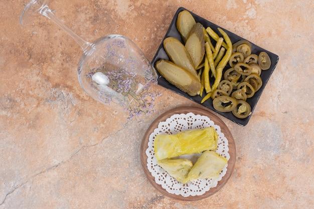 Рулетики долмы из капусты и тарелка солений на оранжевой поверхности.