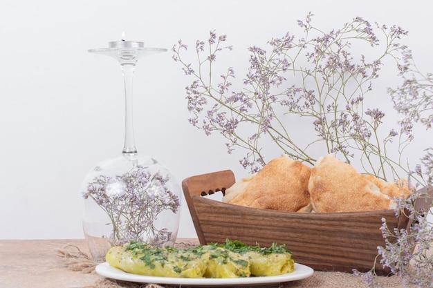 Рулетики долмы капусты на белой тарелке и корзине с хлебом.