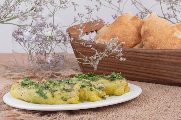 Рулетики долмы из капусты на белой тарелке и корзине с хлебом.