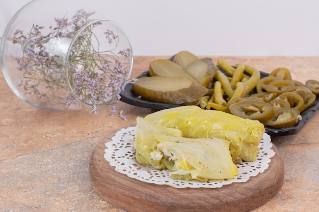 Cabbage dolma rolls and plate of pickles on orange surface.