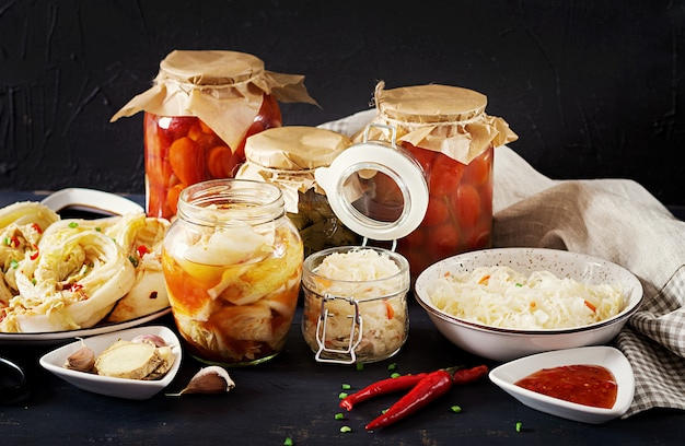 Cabbage kimchi, tomatoes marinated, sauerkraut sour glass jars over rustic kitchen table.