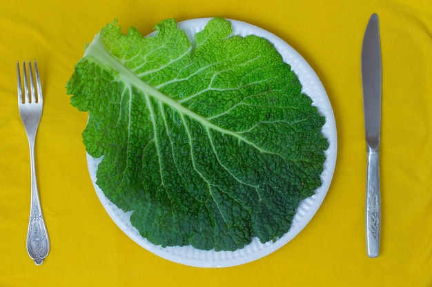 Cabbage leaves on a plate. knife and fork on a yellow background