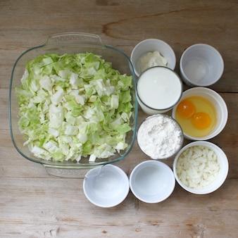 キャベツパイの準備ステップバイステップのレシピ食材の材料を木製のテーブルトップビューフラットレイに。閉じる。セレクティブフォーカス。コピースペース