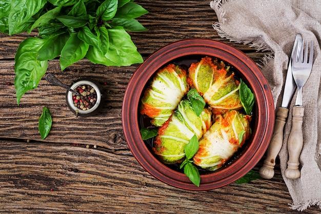 Голубцы фаршированные рисом с куриным филе в томатном соусе на деревянном столе. вкусная еда. вид сверху. плоская планировка