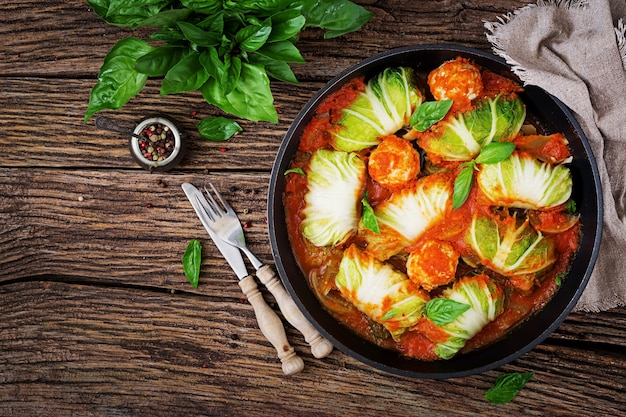 Cabbage rolls stuffed with rice with chicken fillet in tomato sauce on a wooden background.