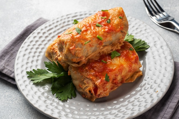 Cabbage rolls with beef, rice and vegetables on the plate. stuffed cabbage leaves with meat. gray concrete table