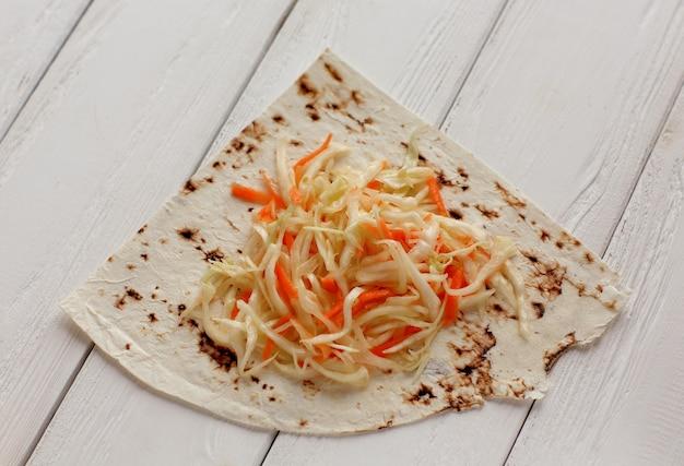 木製のテーブルにキャベツのサラダとピタパン。