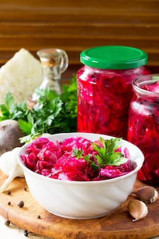 Cabbage salad with beetroot on the kitchen wooden table