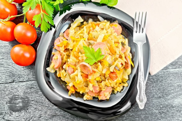 Cabbage stew with sausages in a black plate, napkin, tomatoes, parsley and fork on a wooden board background from above
