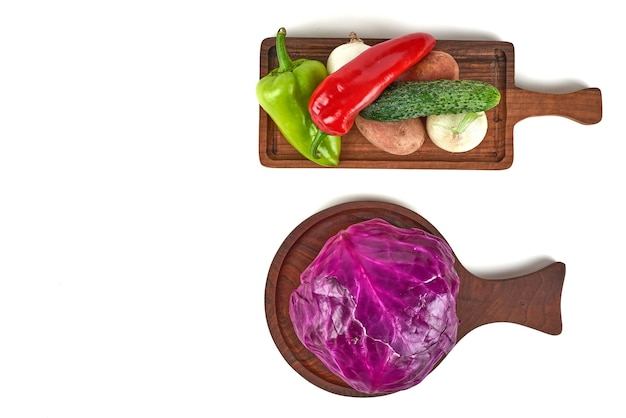 Cabbage and vegetables on a wooden platter.