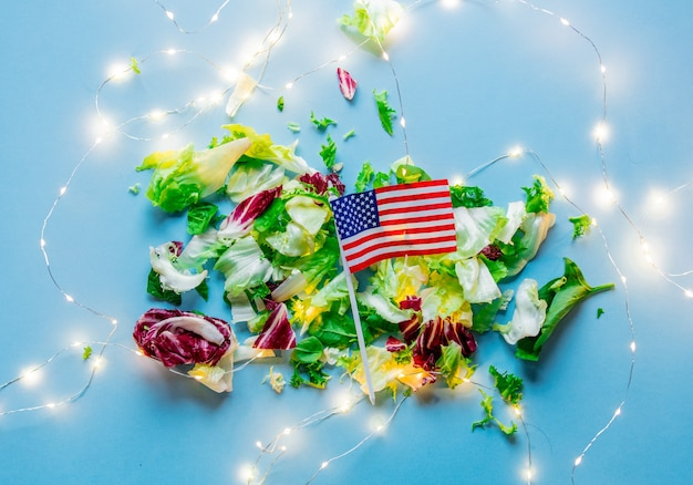 Cabbage with usa flag and holiday fairy lights on blue surface. above view