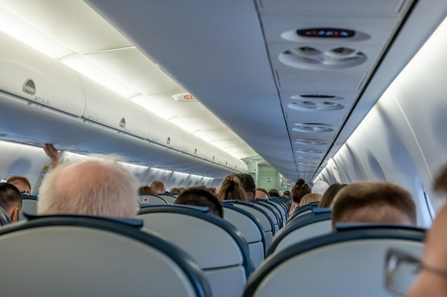 In the cabin of aircraft. passengers in the cabin of the aircraft. commercial airplane cabin with rows of seats down the aisle. cabin of modern aircraft with passengers on seats