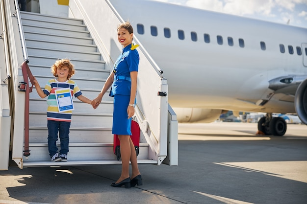 Cabin attendant standing with a boy at a boarding ramp