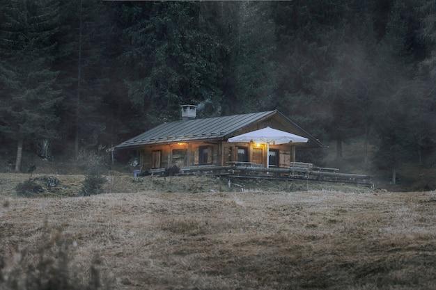 Cabina da un bosco con trama di sovrapposizione di nebbia