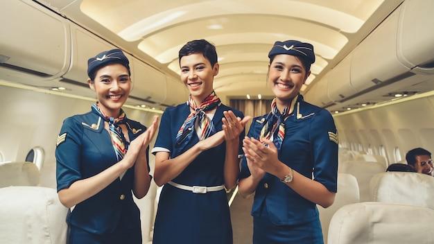 飛行機の中で手をたたく客室乗務員