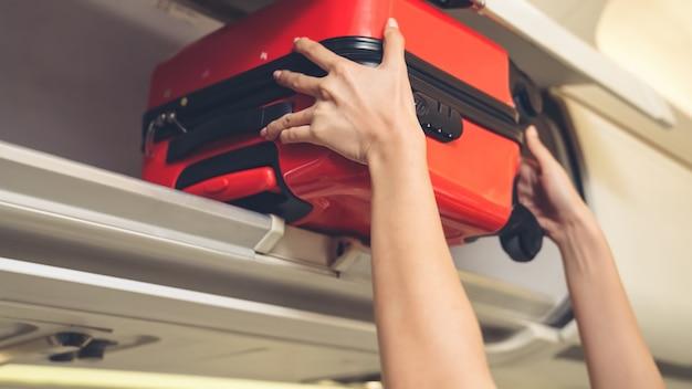客室乗務員が飛行機の中で荷物バッグを持ち上げる
