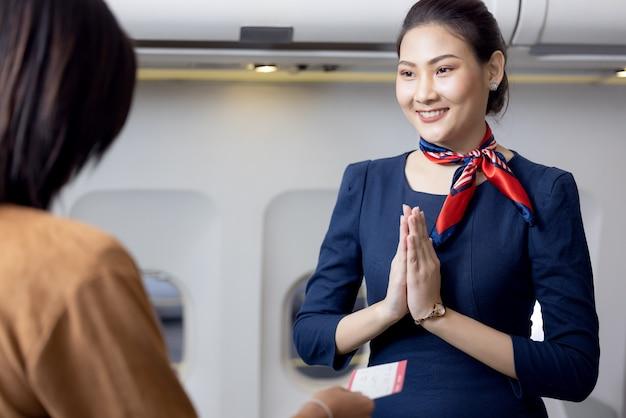 기내 승무원 또는 스튜어디스가 비행기, 항공 스튜어디스 또는 스튜어디스 서비스에서 승객을 맞이합니다.