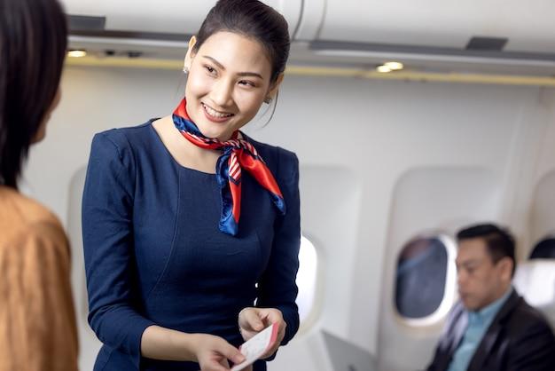飛行機の乗客に挨拶する客室乗務員またはスチュワーデス、エアホステスまたはスチュワーデスサービス