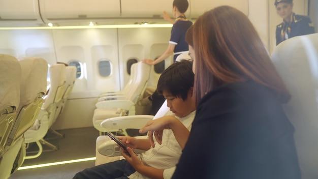 客室乗務員は飛行機の中で家族にサービスを提供します。航空輸送と観光の概念。