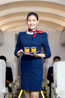 Cabin crew serve water to passenger in airplane . airline transportation and tourism concept.