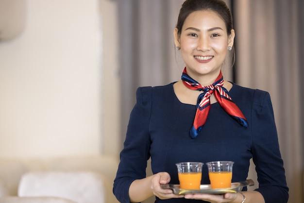 객실 승무원은 비행기 승객에게 물을 제공합니다. 항공 운송 및 관광 개념.