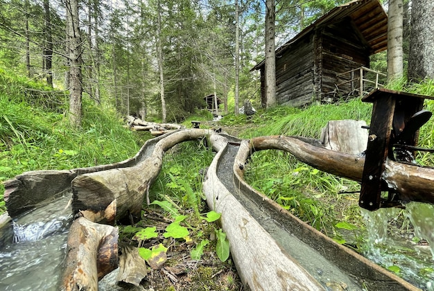 Домик в лесу с небольшими водопадами в деревянных бревнах