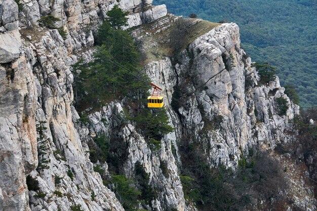 ロープウェイのキャビンは、急な岩の崖を背景に移動します