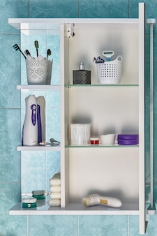 Cabinet with door for bathroom with toiletries on  shelves.