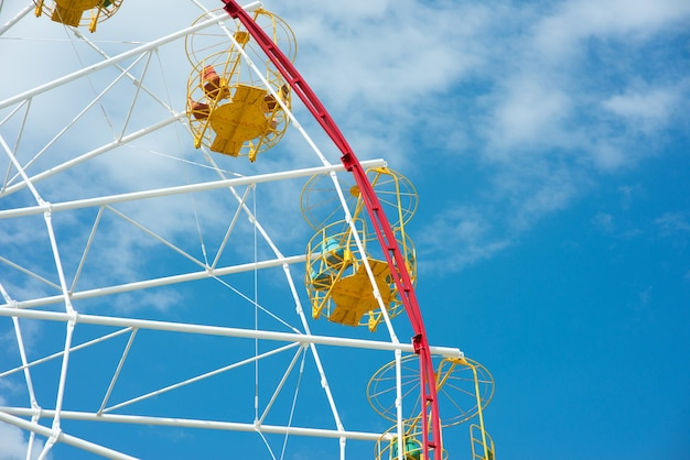 Cabins ferris wheel against a blue sky with clouds
